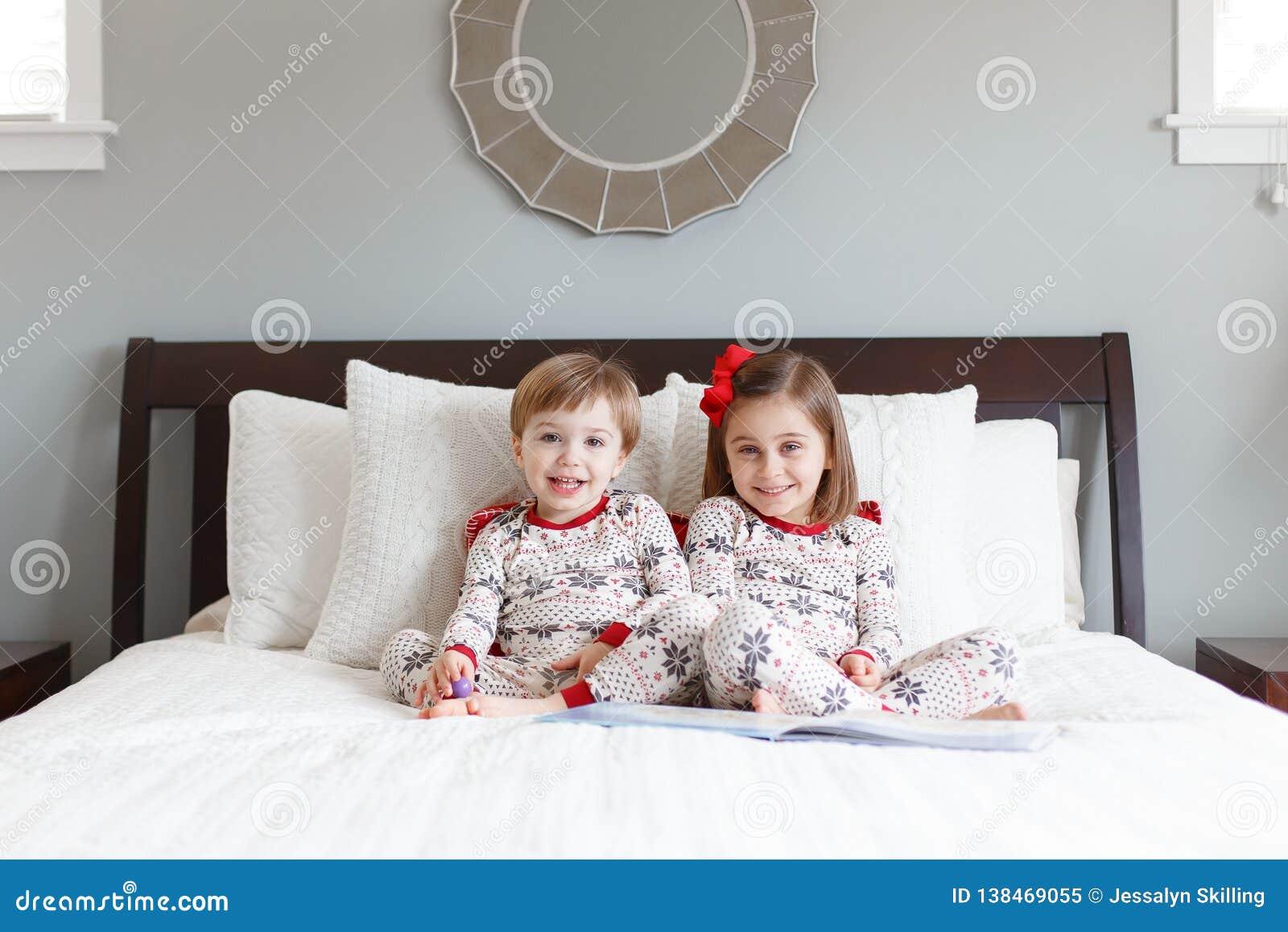 Ragazzo e ragazza sul letto con i pigiami di Natale
