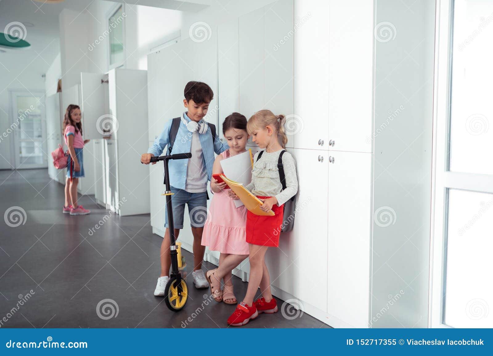 Ragazzo e ragazze che stanno vicino agli armadi mentre avendo rottura dalla lezione