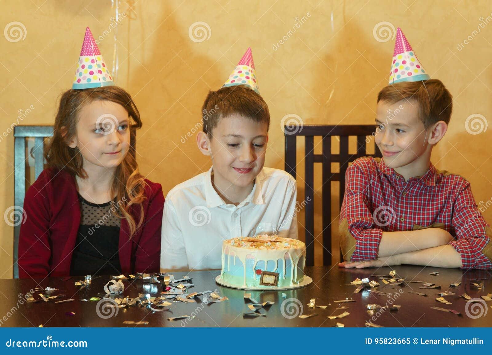 Ragazzo ed amici che esaminano torta di compleanno torta di compleanno sulla tavola di festa a children& x27; partito di s