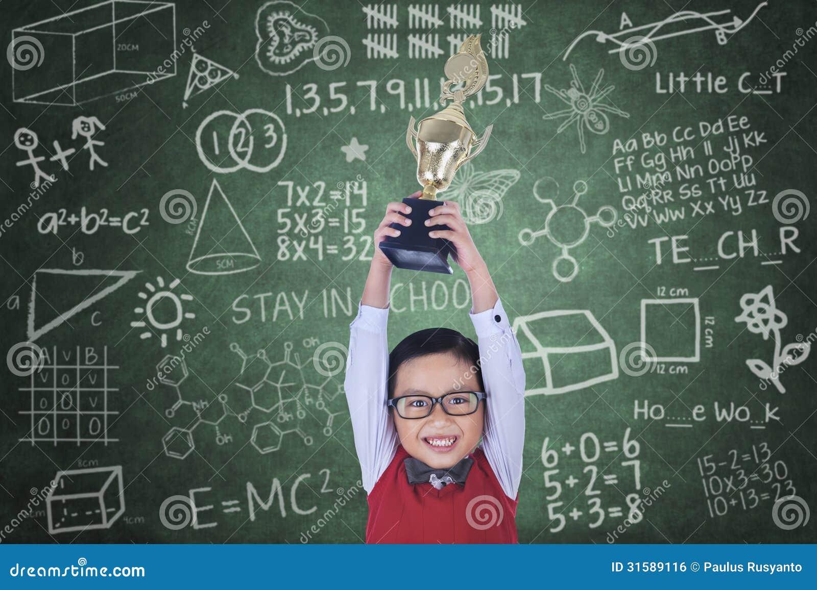 Ragazzo felice che alza trofeo nella classe