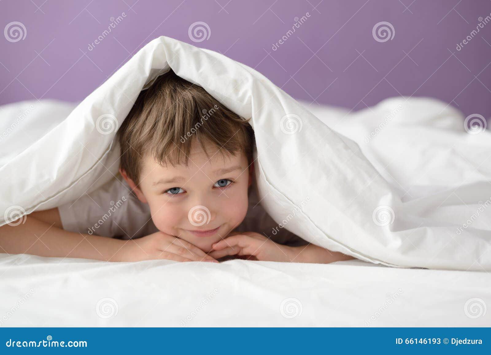 Ragazzo felice che si nasconde a letto sotto una coperta o un copriletto bianca