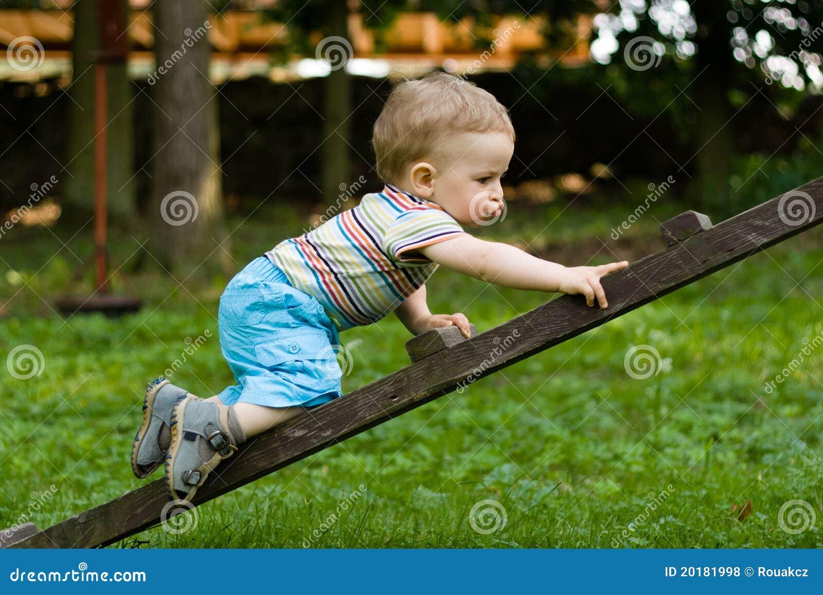 Ragazzo felice che striscia sulla scaletta