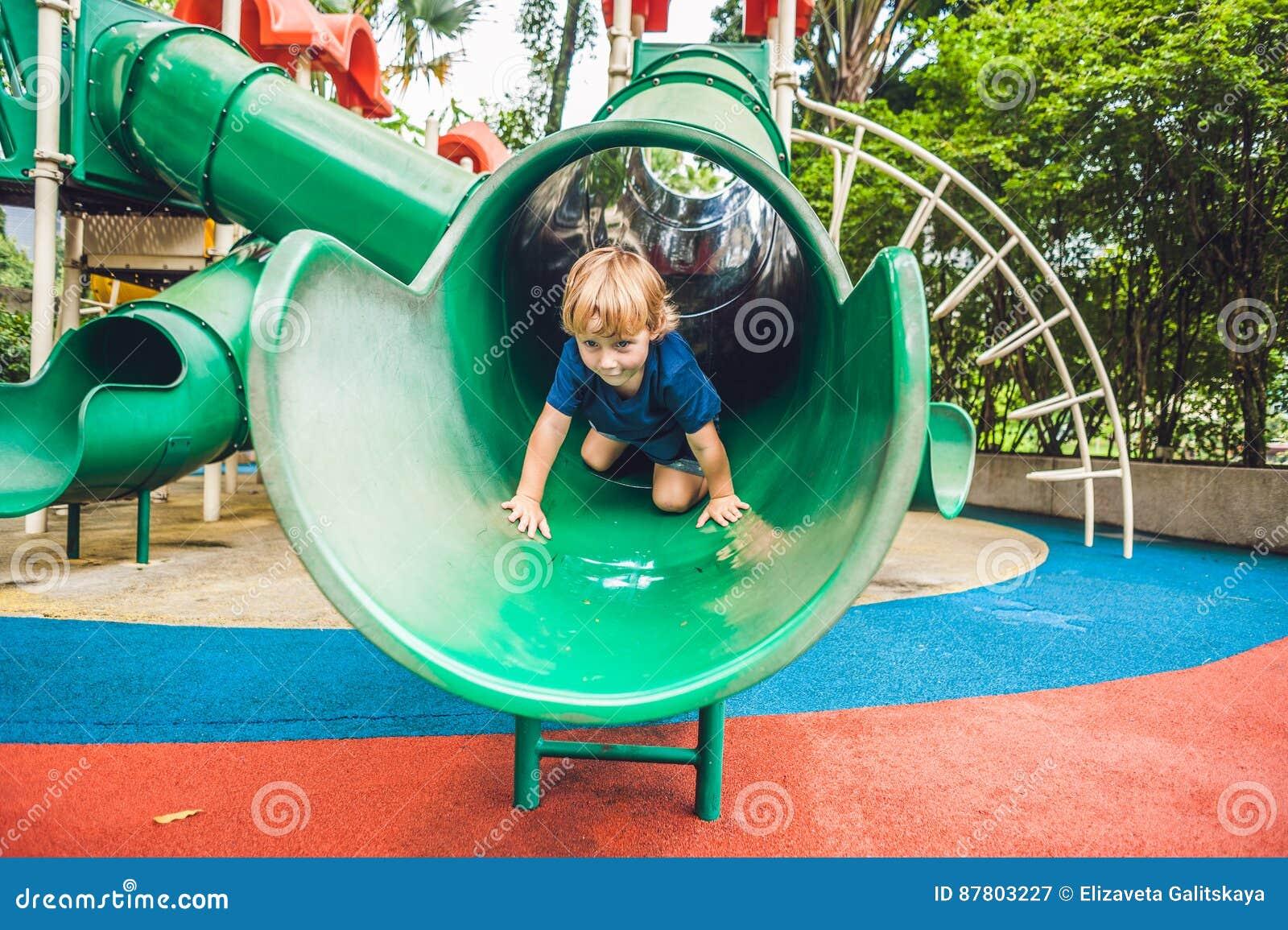 Ragazzo felice del bambino che gioca al campo da giuoco variopinto Bambino adorabile divertendosi all aperto