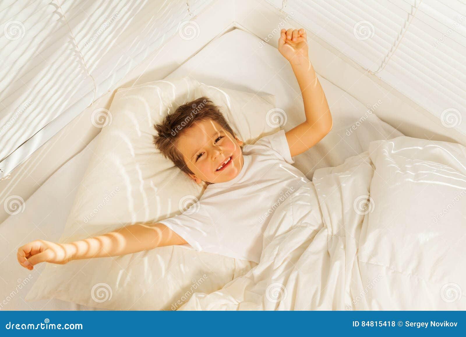 Ragazzo felice del bambino che sveglia nella sua camera da letto bianca fotografia stock - Letto che si chiude ...
