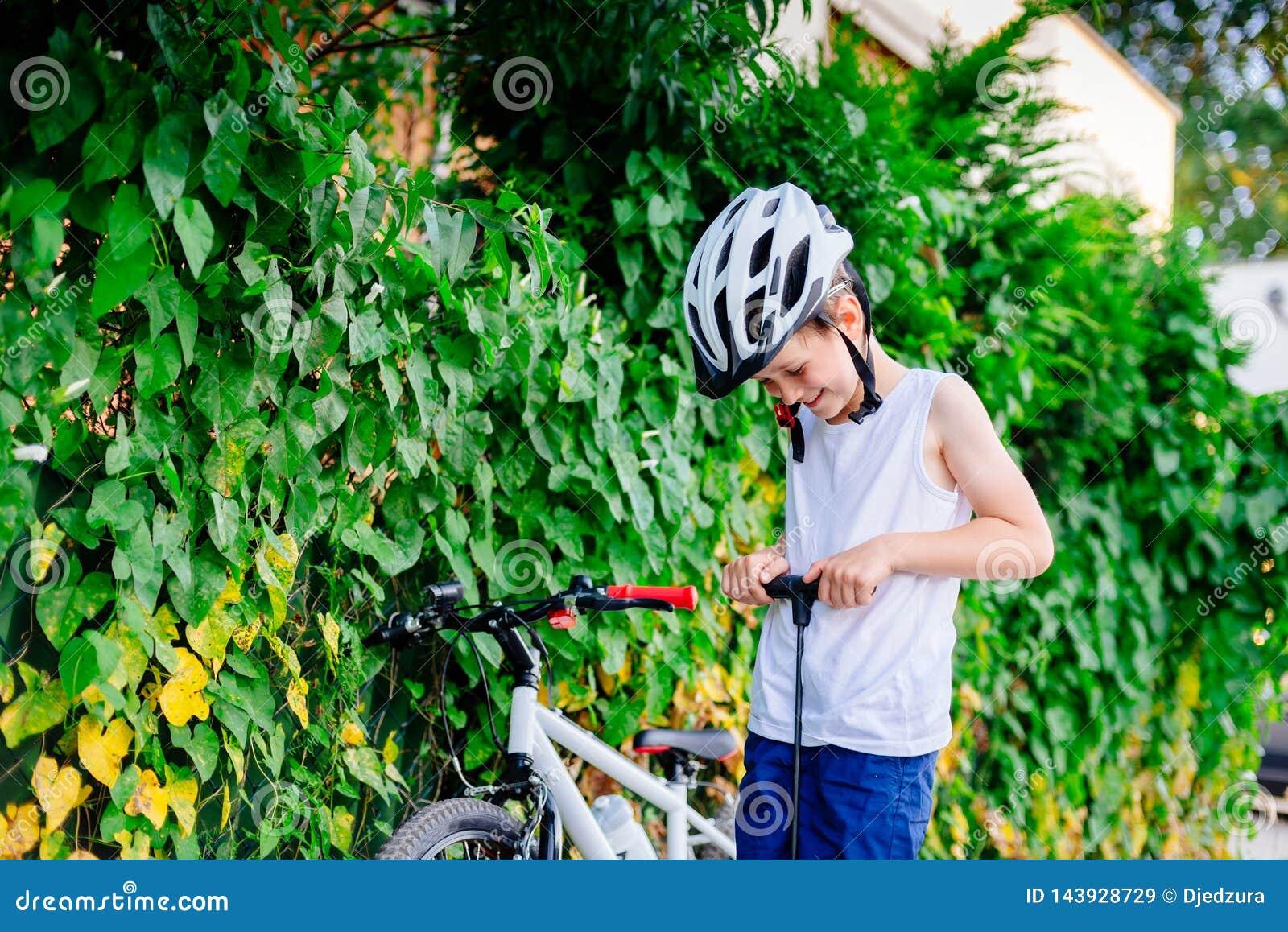 Ragazzo felice del piccolo bambino in casco bianco che gonfia gomma in sua bicicletta