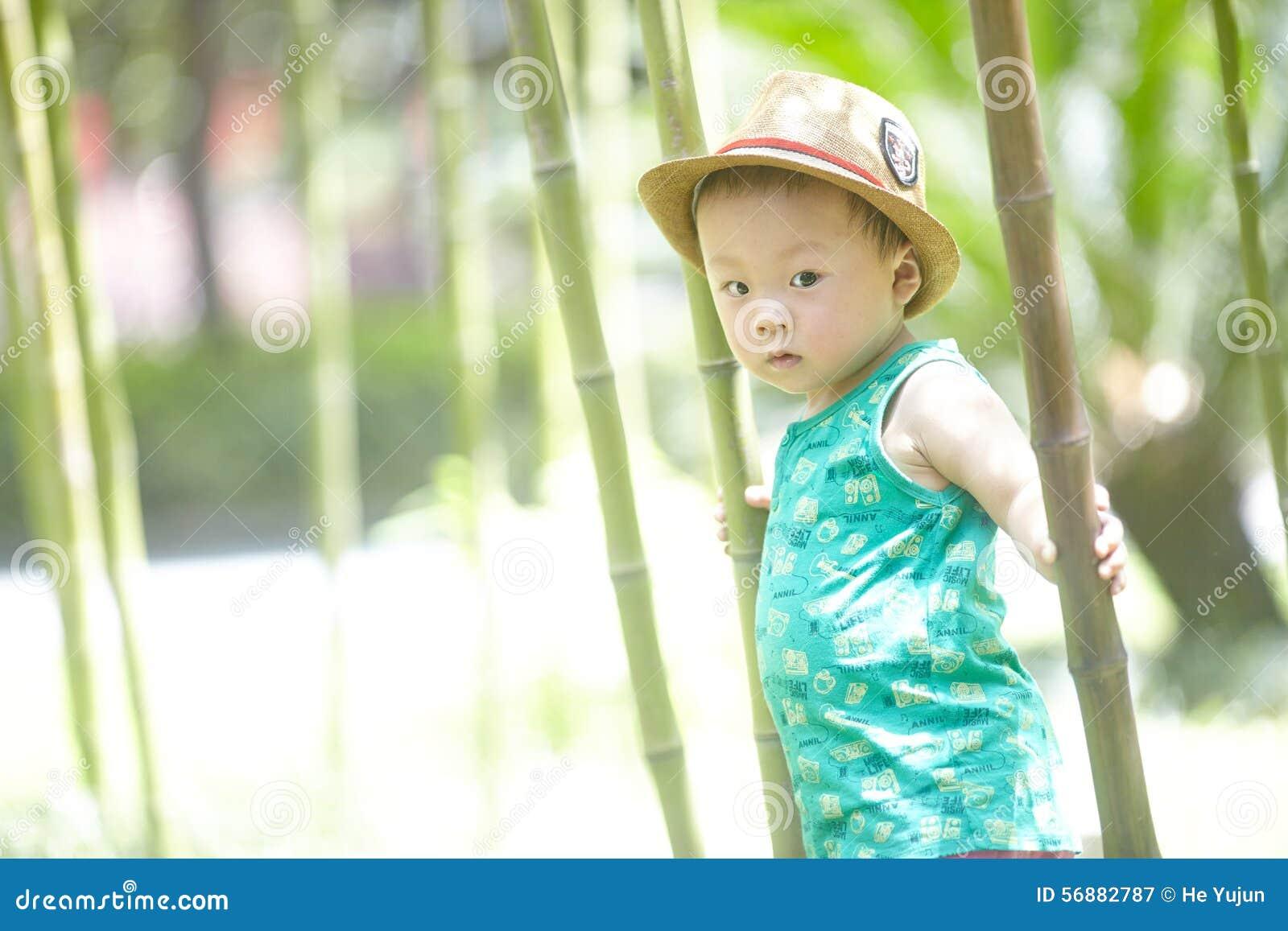Ragazzo in foresta di bambù di estate
