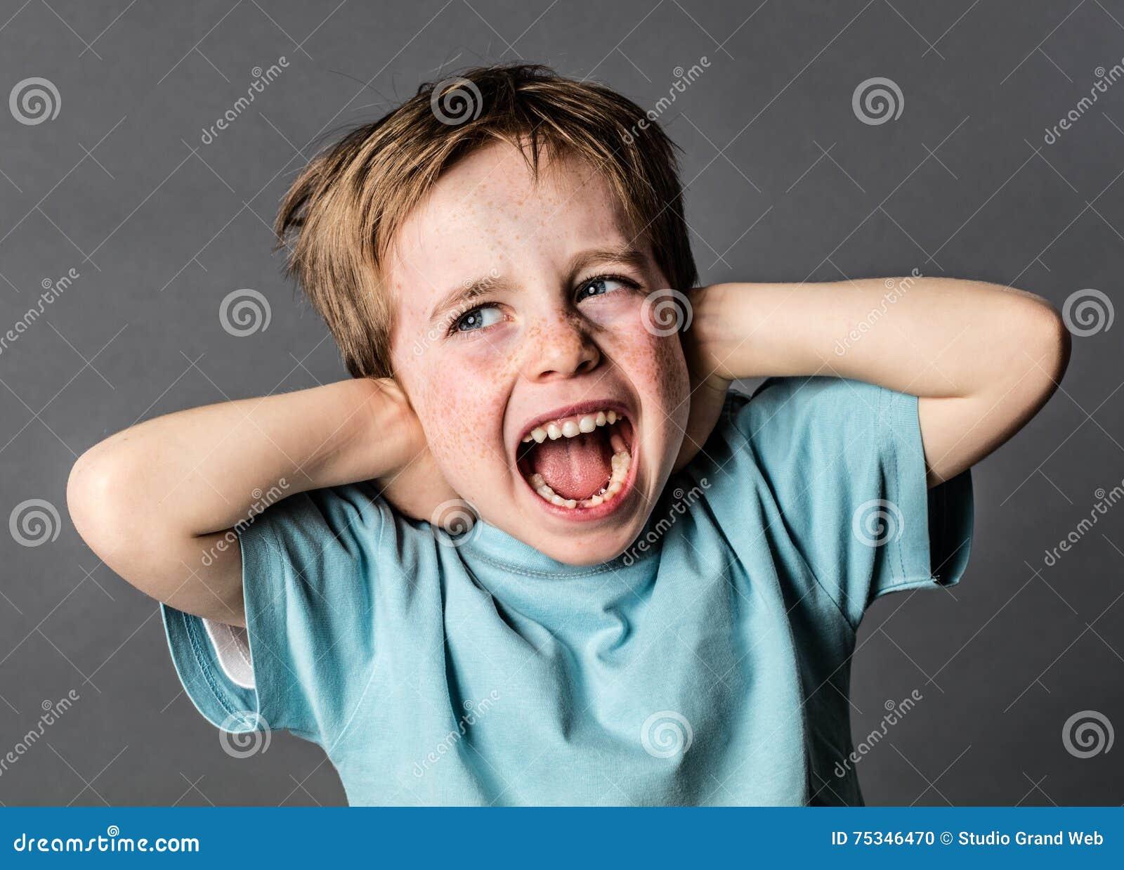 Ragazzo giovane di grido che soffre dal dolore domestico che copre le sue orecchie