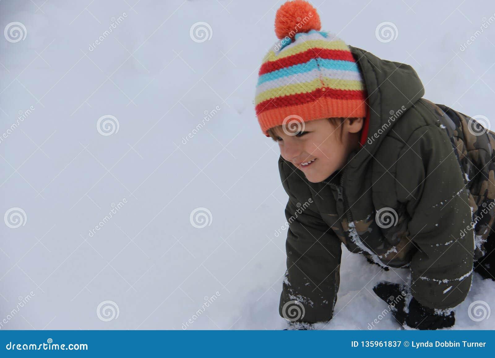 Ragazzo indigeno che ha divertimento della neve di inverno nella prateria