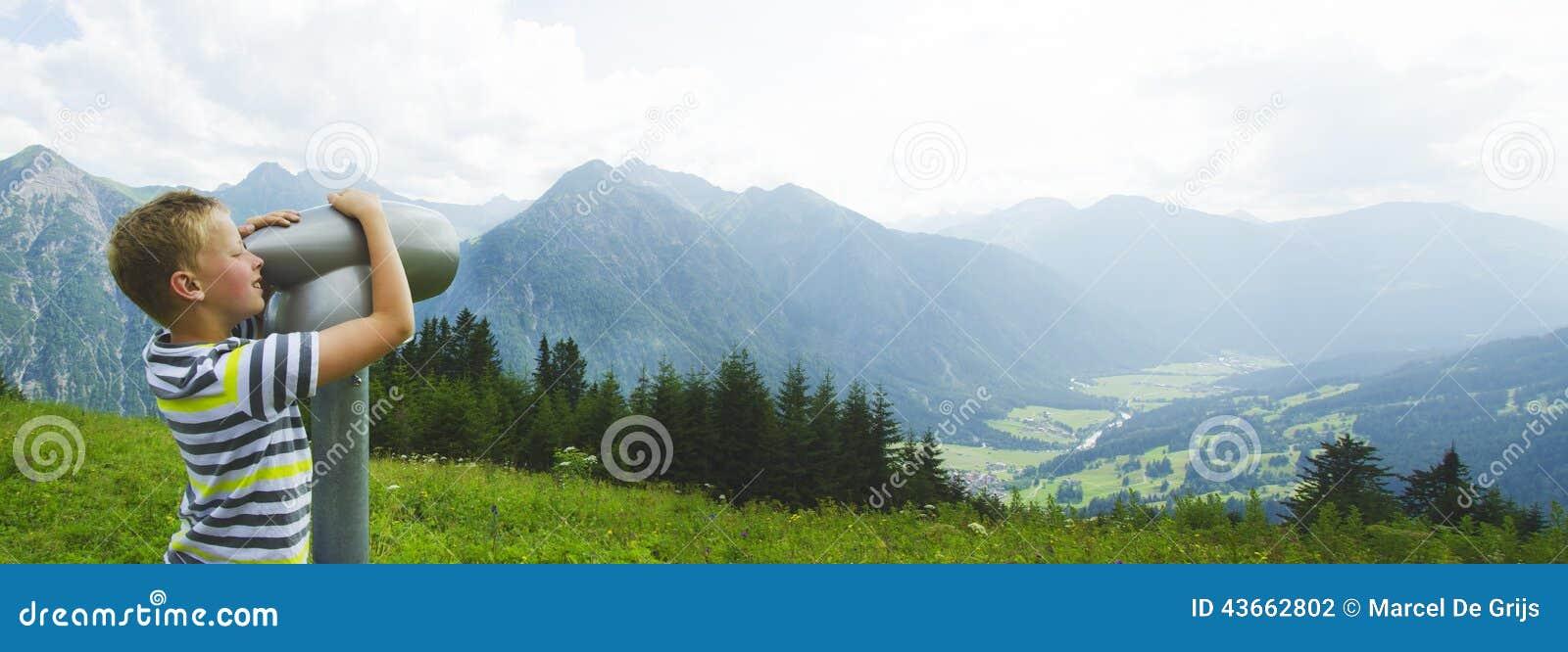 Ragazzo in montagne che guardano attraverso il vetro di sguardo