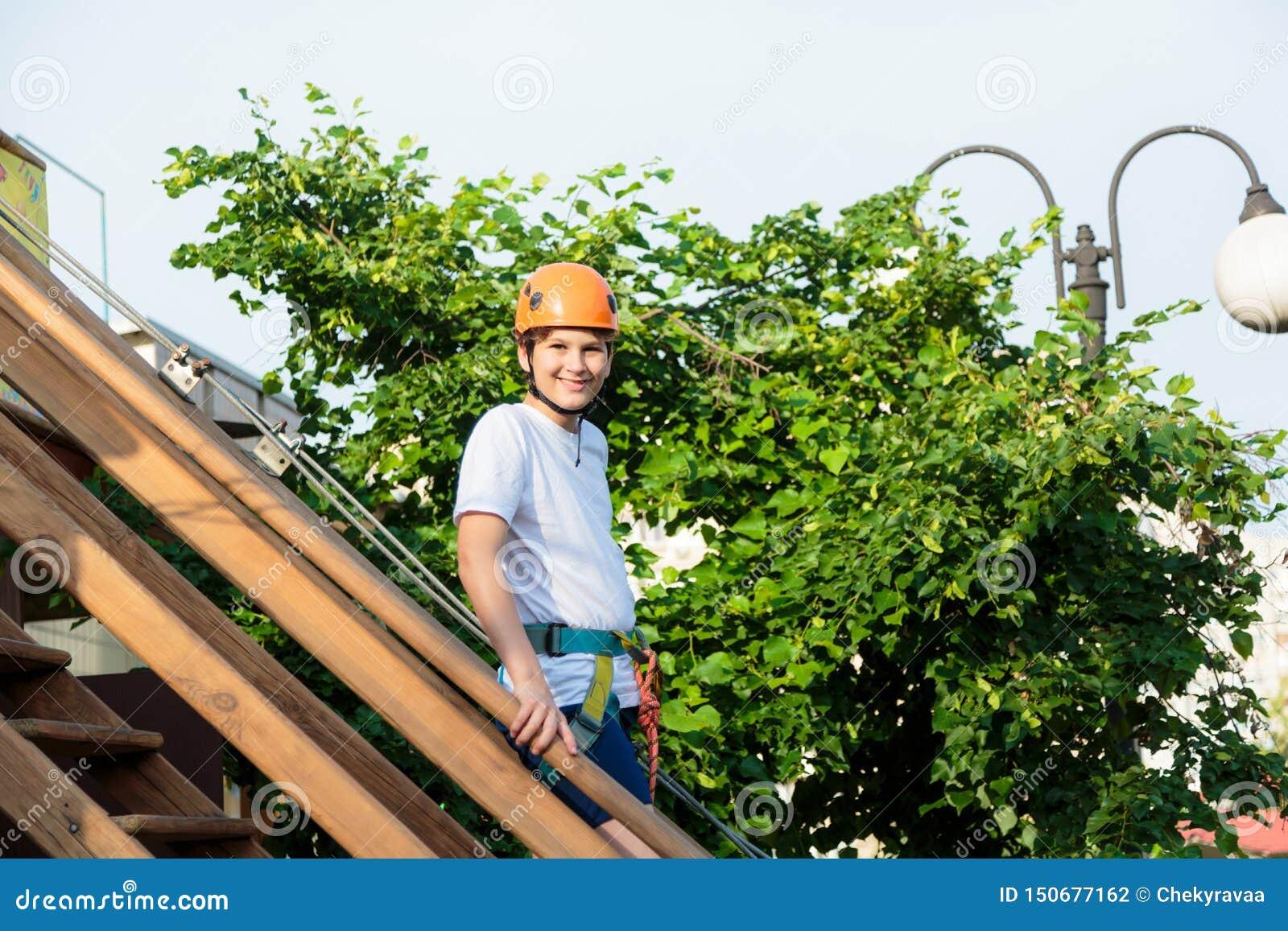 Ragazzo nel parco di avventura della foresta Bambino in casco arancio e salite bianche della maglietta sull alta traccia della co