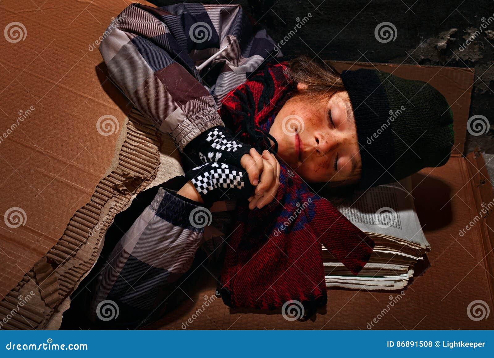Ragazzo povero del mendicante che prepara dormire sulla via - coperta