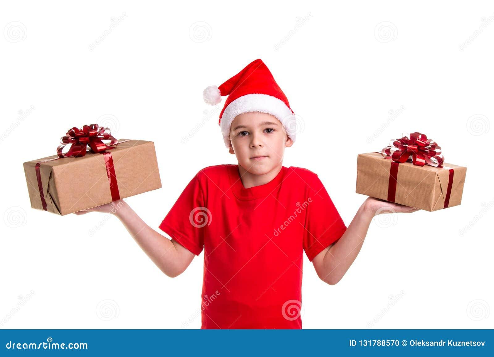 Ragazzo serio bello, cappello di Santa sulla sua testa, con due contenitori di regalo sulle mani, imbarazzate per fare un choise