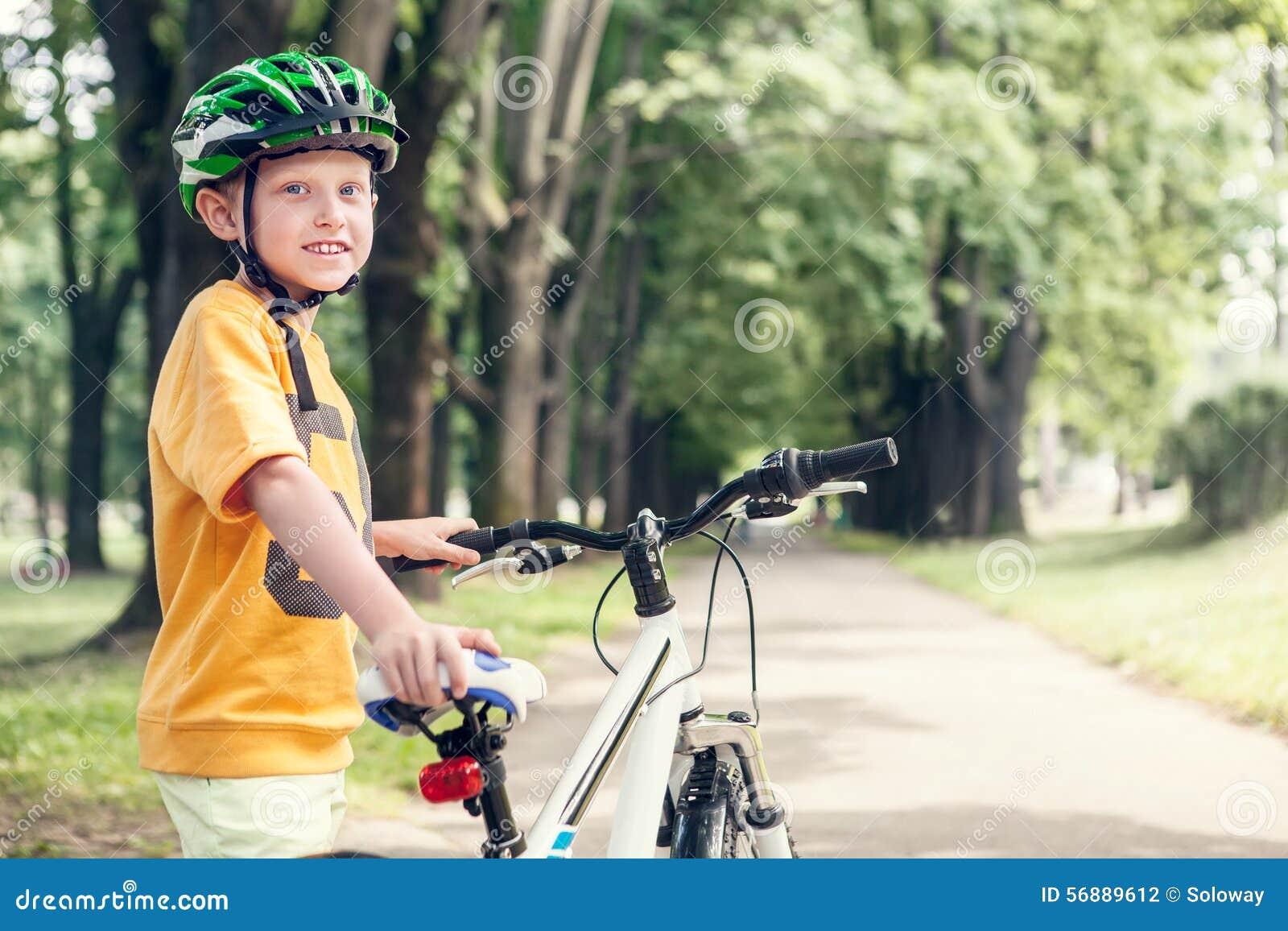 Ragazzo sorridente con la nuova bicicletta in parco