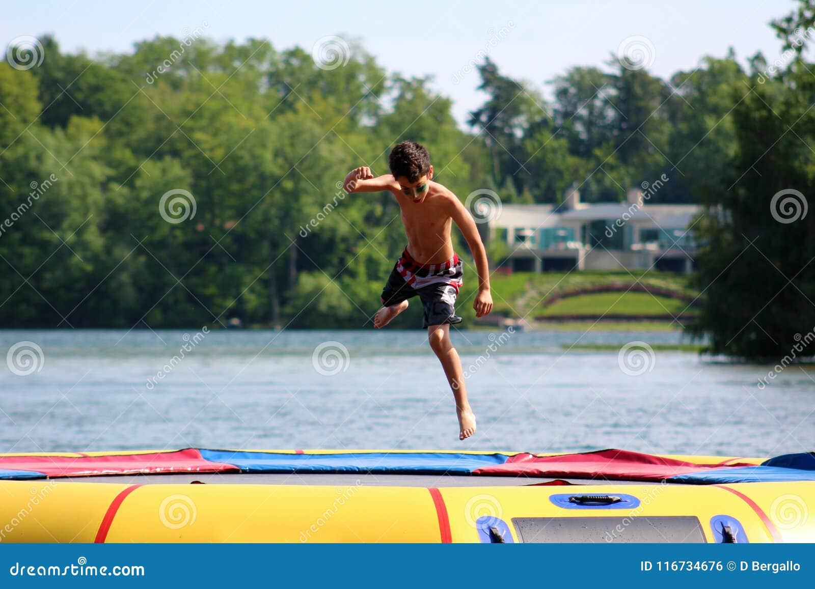 Ragazzo sveglio bello che salta ad un trampolino dell acqua che galleggia in un lago nel Michigan durante l estate