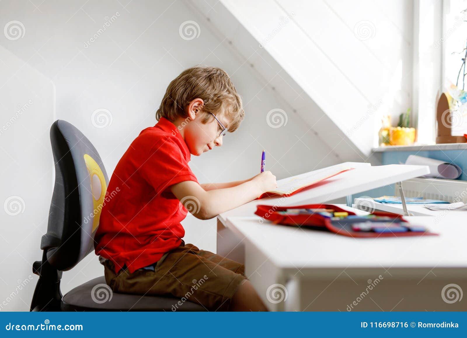 Ragazzo sveglio del bambino con i vetri a casa che fanno compito, scrivente le lettere con le penne variopinte