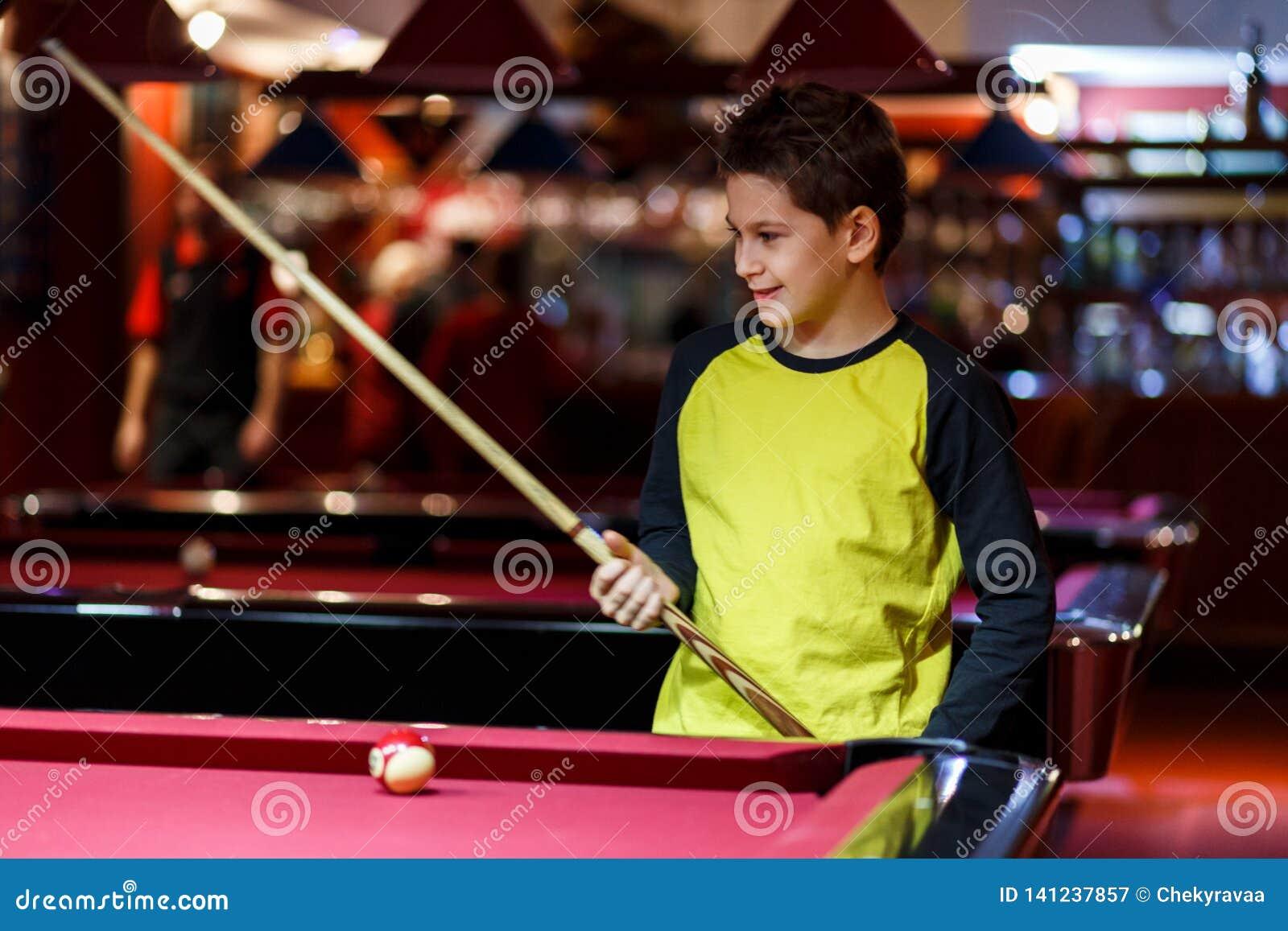 Ragazzo sveglio nel biliardo giallo dei giochi della maglietta o stagno in club Il ragazzino impara giocare lo snooker Ragazzo co
