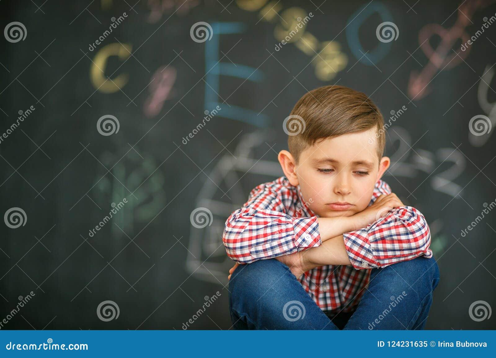 Ragazzo triste che si siede con gli occhi chiusi contro lo sfondo del consiglio scolastico