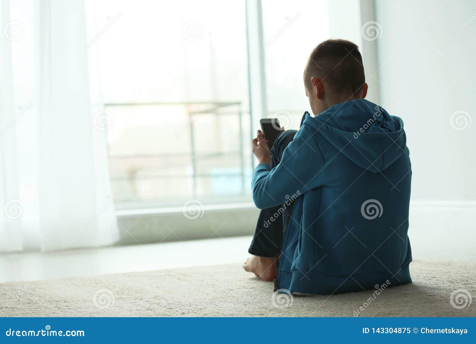 Ragazzo turbato con lo smartphone che si siede vicino alla finestra all interno