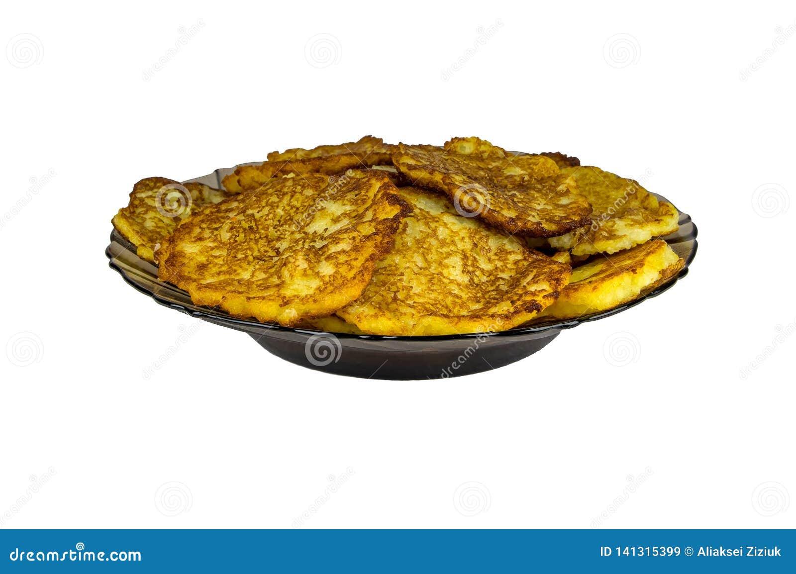 Raggmunkar på en svart platta som isoleras Grated stekte potatisar