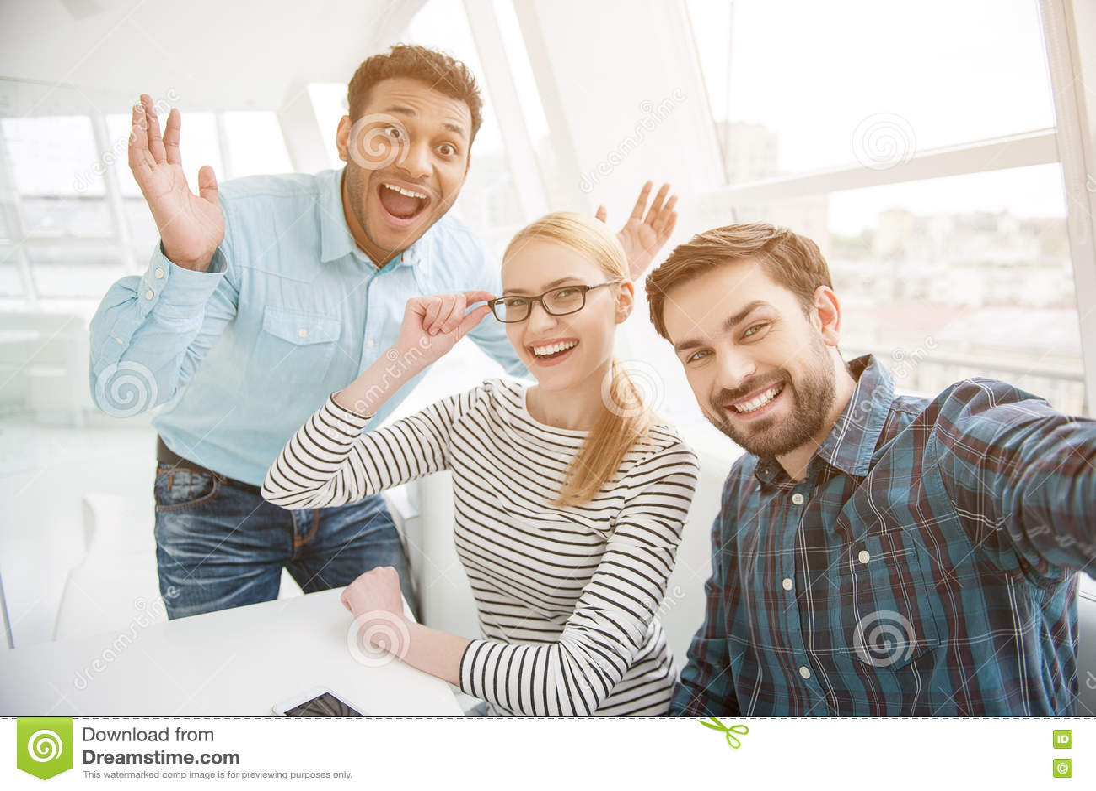 Raggruppi il colpo dei colleghi divertendosi nel loro ufficio