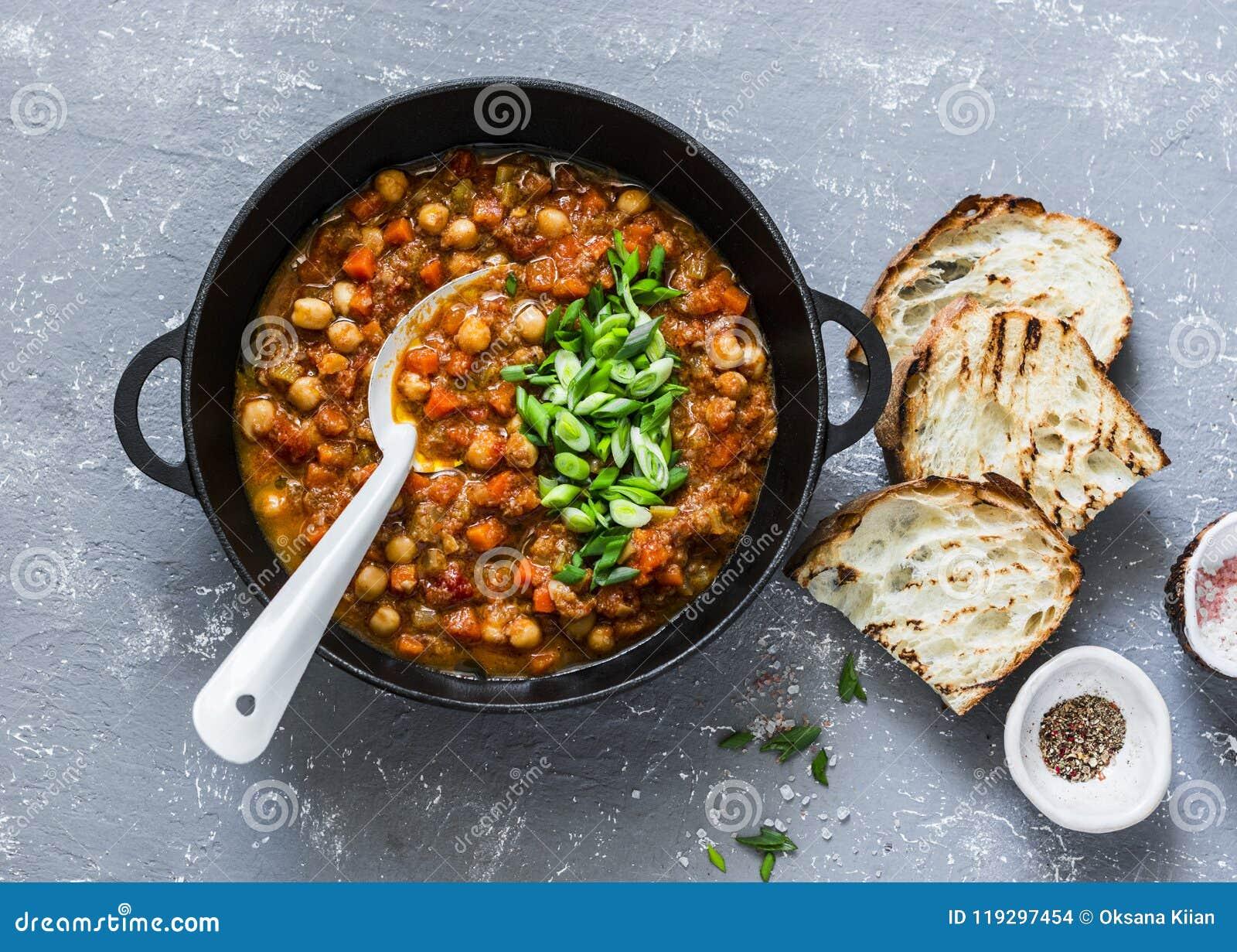 Ragoût de pois chiche de champignons de végétarien dans une casserole de fer et un pain grillé rustique sur un fond gris, vue sup