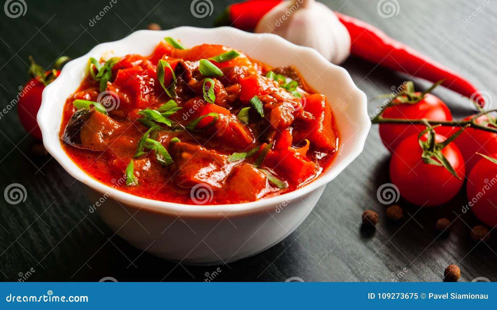 Rague végétal avec l aubergine, le poivre, la tomate et la carotte dans la cuvette blanche sur le fond en bois foncé