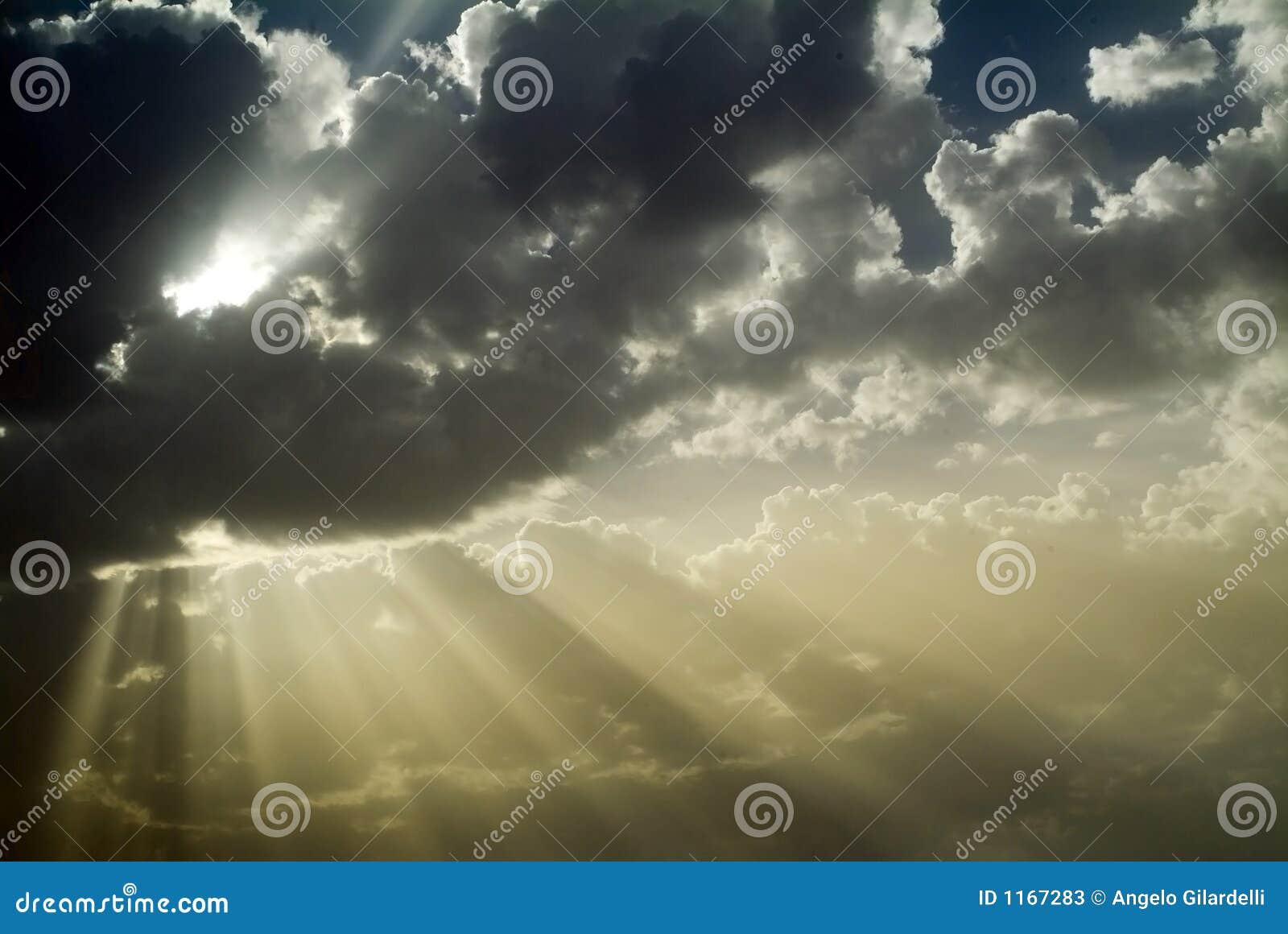 Raias de Sun atrás das nuvens