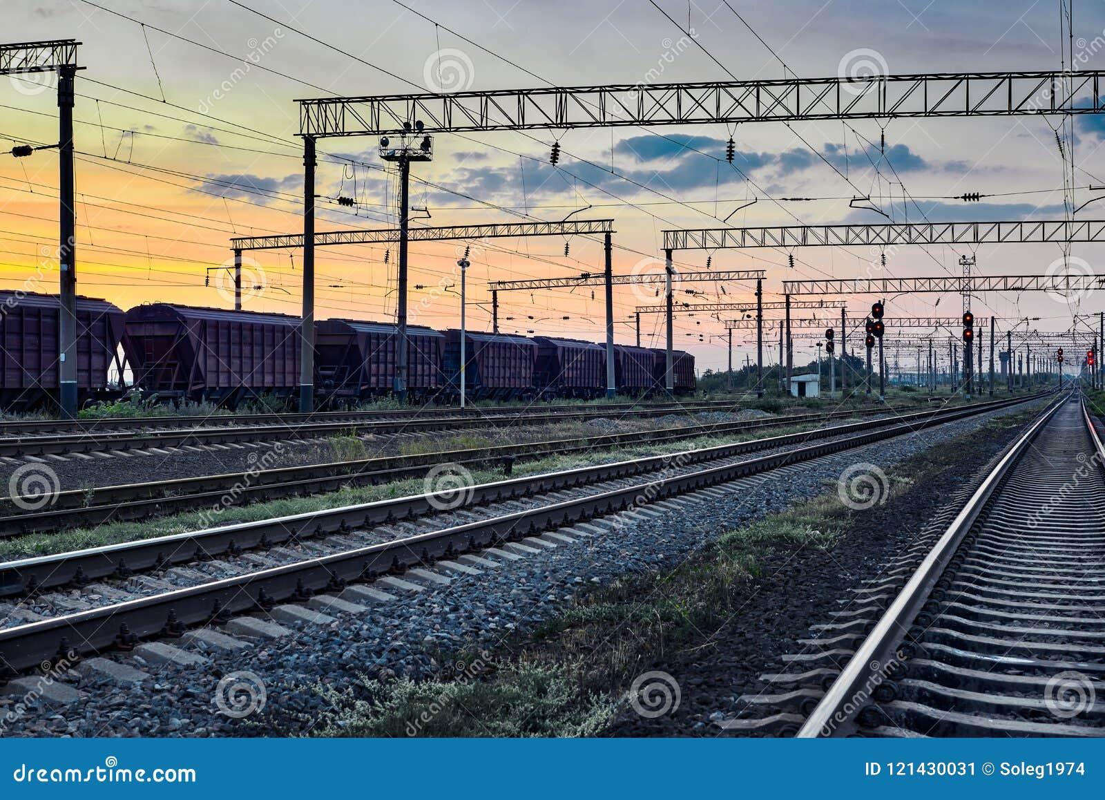 Railcar voor droge lading tijdens mooie zonsondergang en kleurrijke hemel, spoorweginfrastructuur, vervoer en industrieel concept