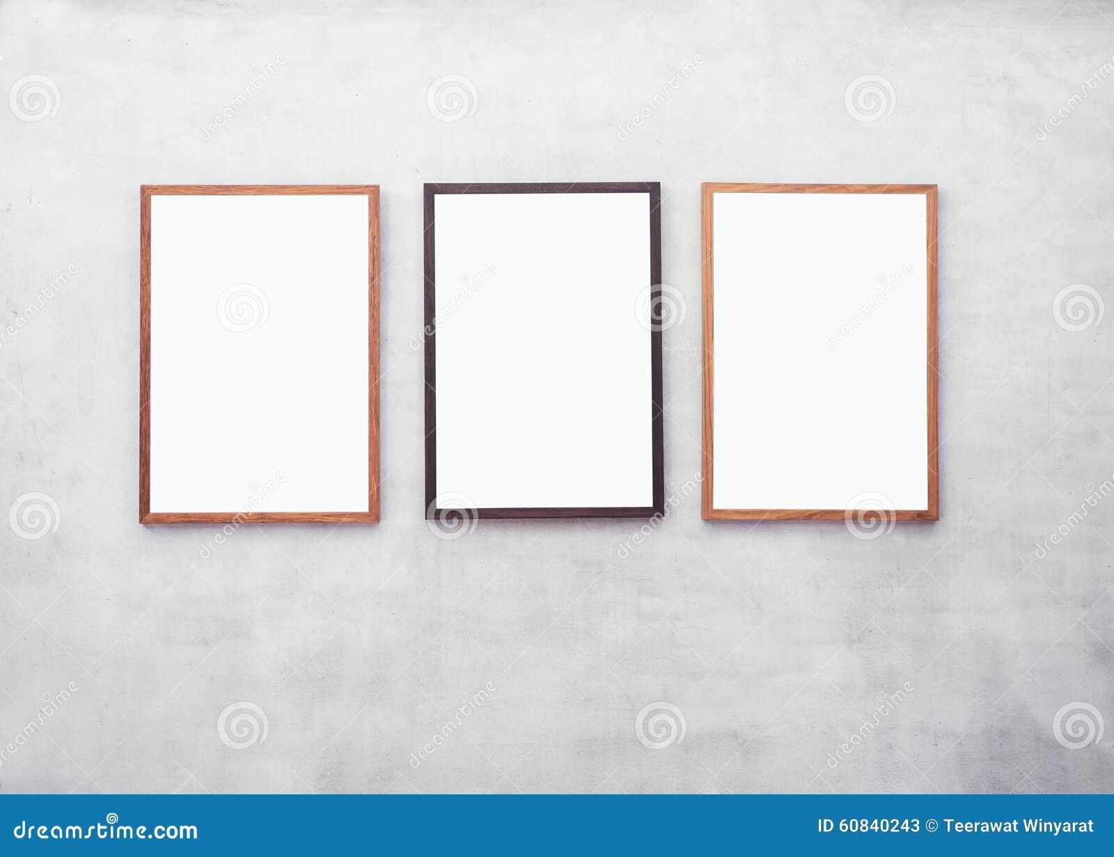 Raillez vers le haut des affiches vides avec le cadre en bois sur le mur de ciment