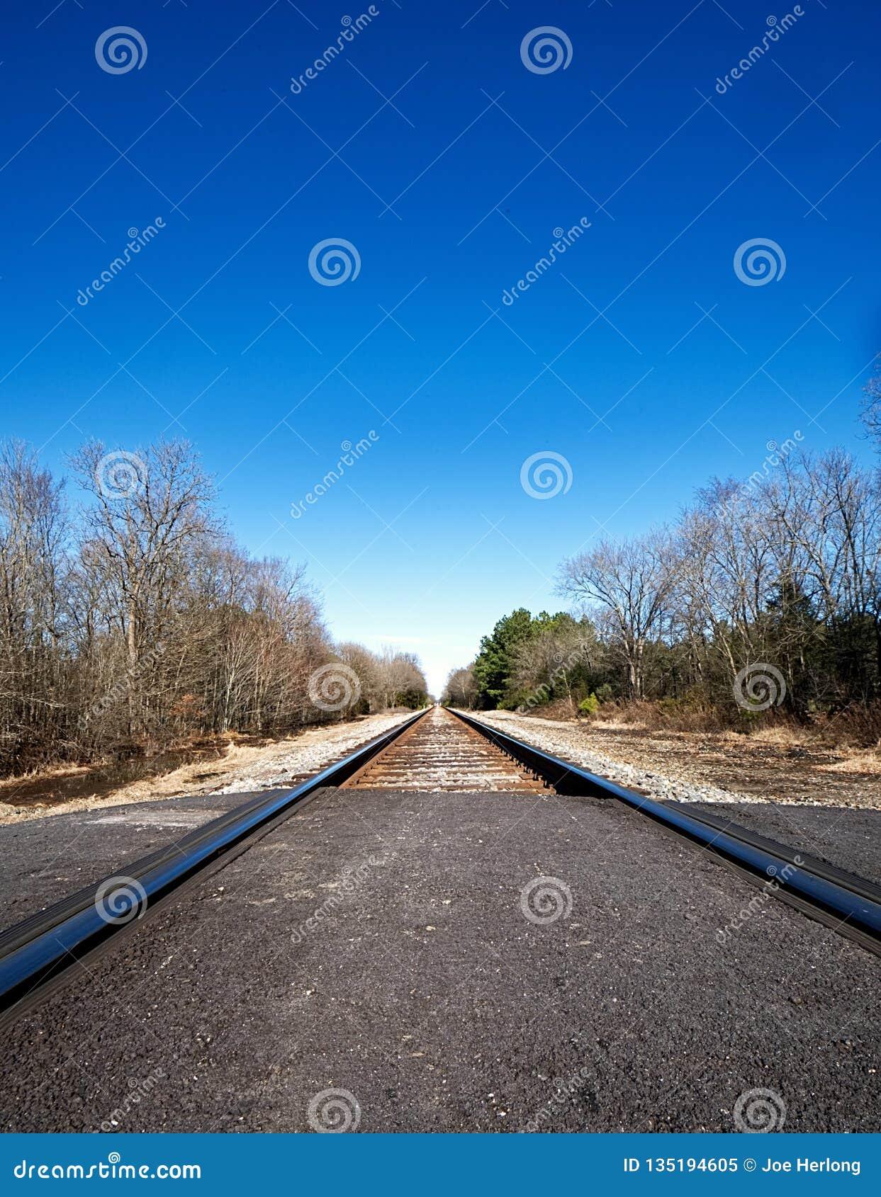 A closeup of railroad tracks leading into infinity and a brilliant blue sky.