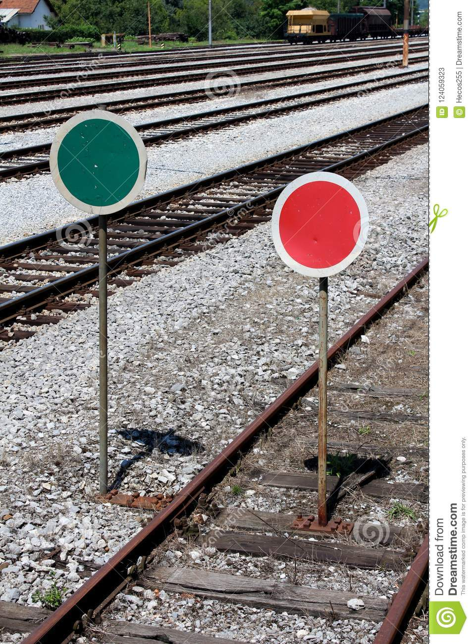 Railway lollipop like signs in green-white and red-white colors mounted on rusted metal poles
