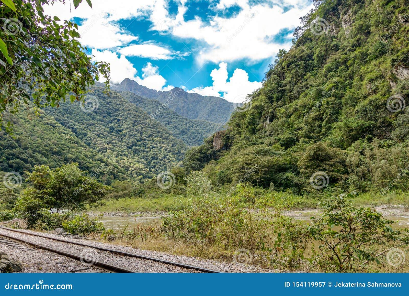Railway to Machu Pichhu inca citadel and peruvian mountains at sunny day