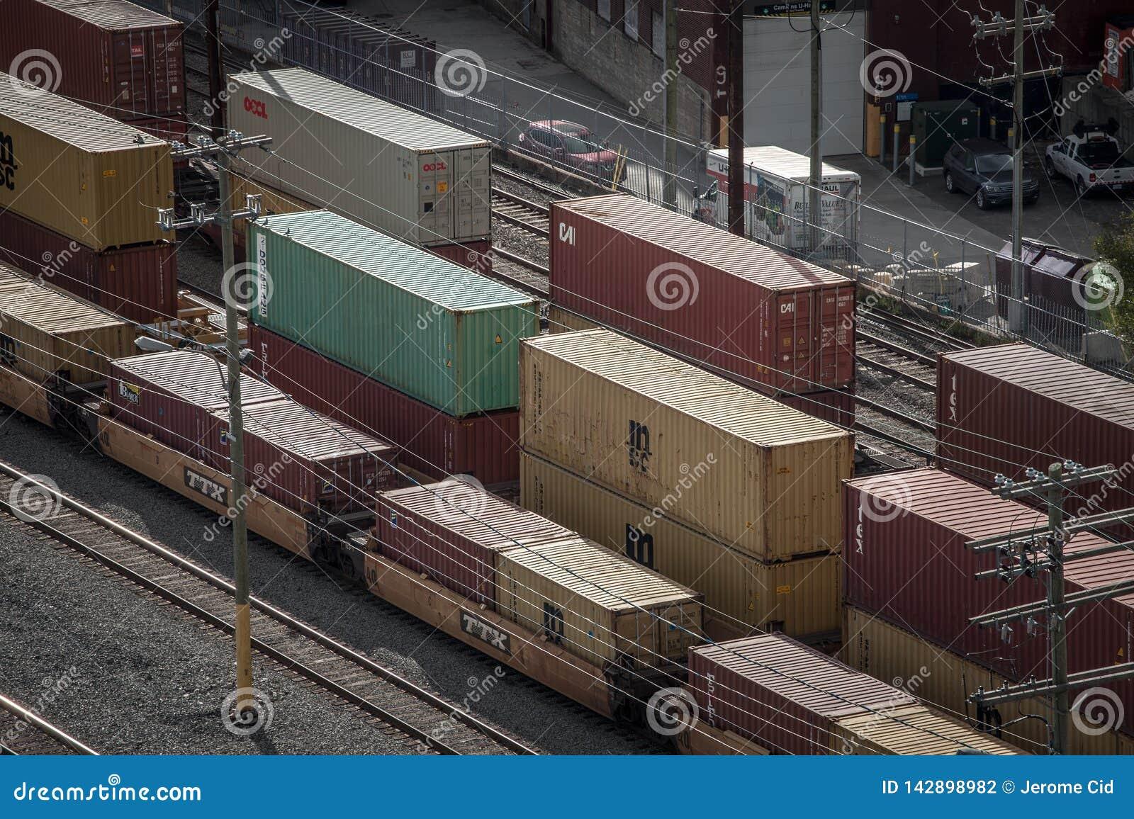 Railyard med behållaredrev från Medelhavs- SändningsFöretag MSC och vagnar som står i den industriella porten av Montreal