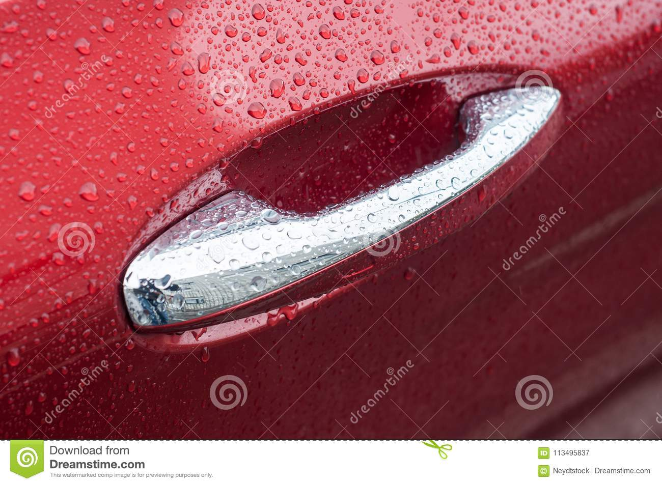 rain drops on chromed handle of red luxury car