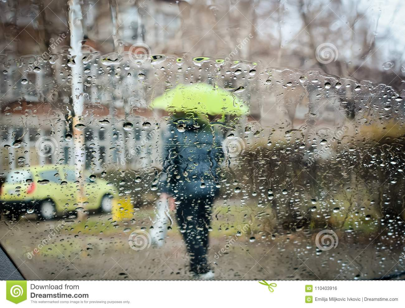 rain drops during falling rain and blurred man with umbrella stock
