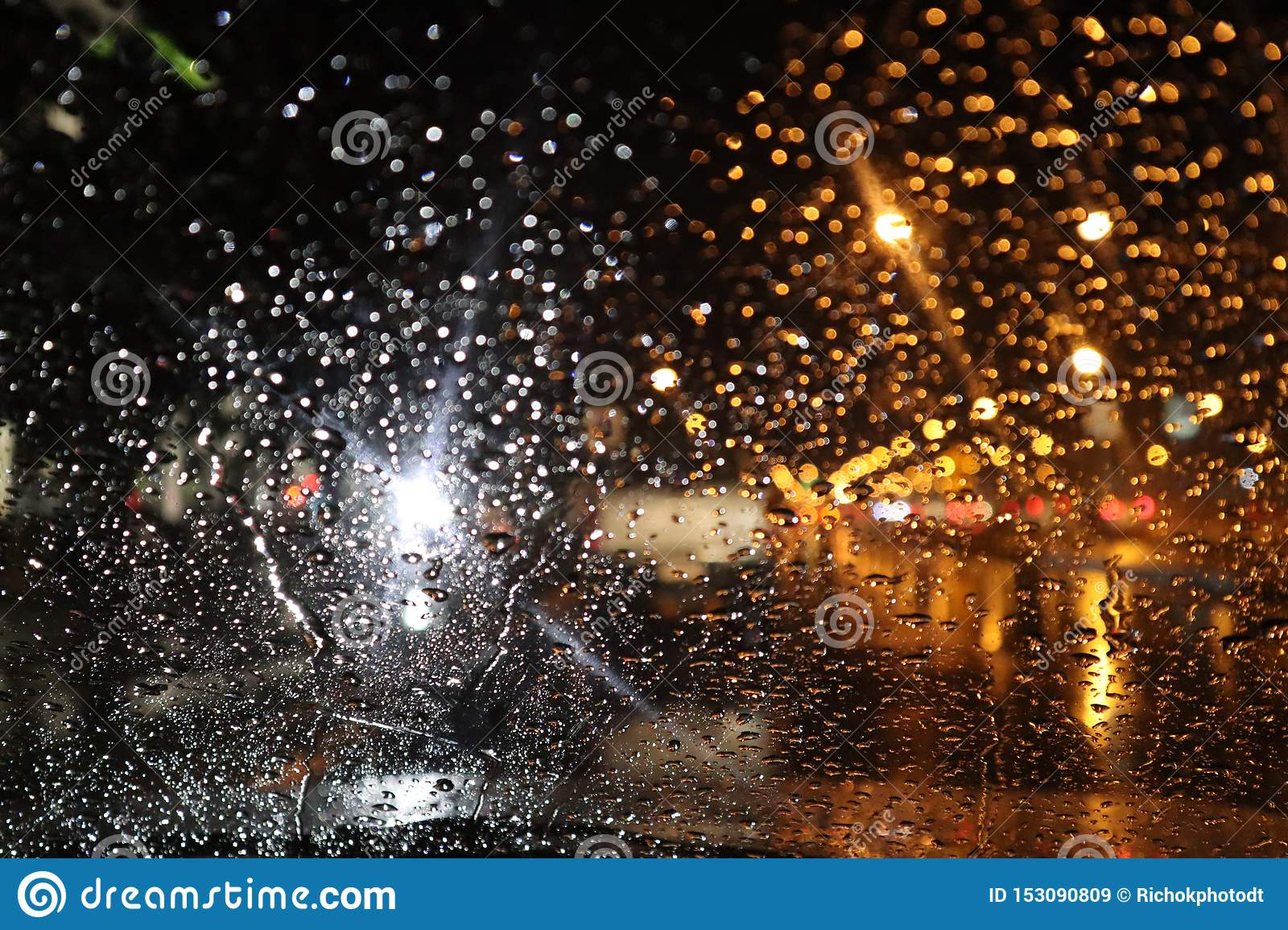 Rain drops on glass of car window with street bokeh at night in rainy season