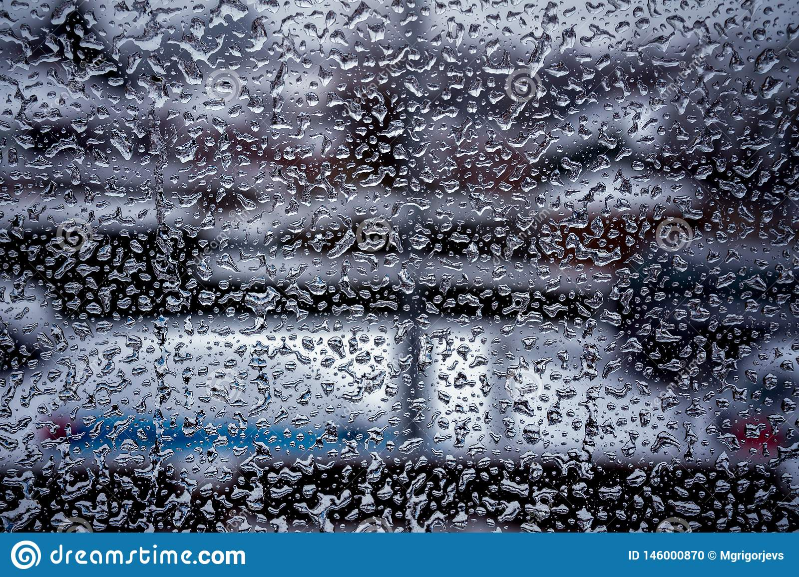 Rain drops on window glass surface with cloudy background