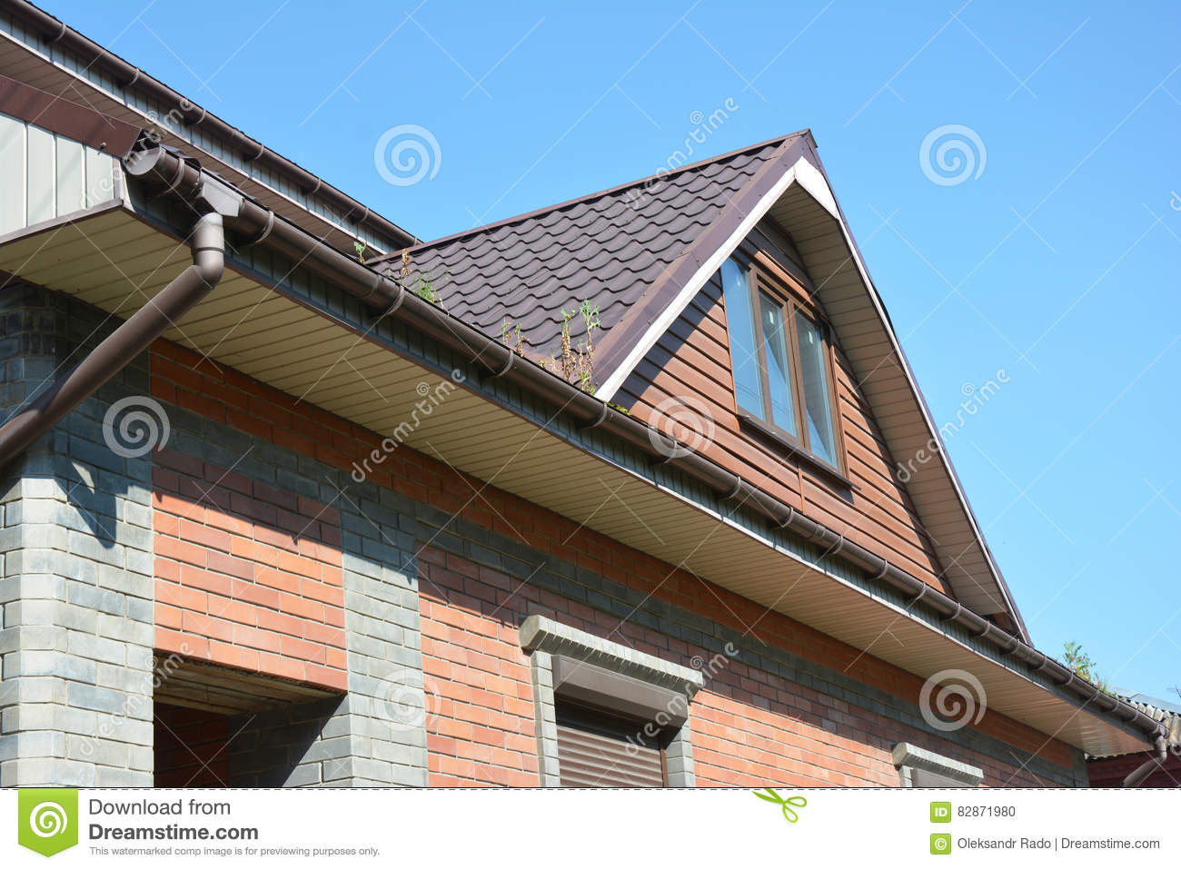 Man cleaning rain gutters inspecting house roof royalty for Does a house need gutters