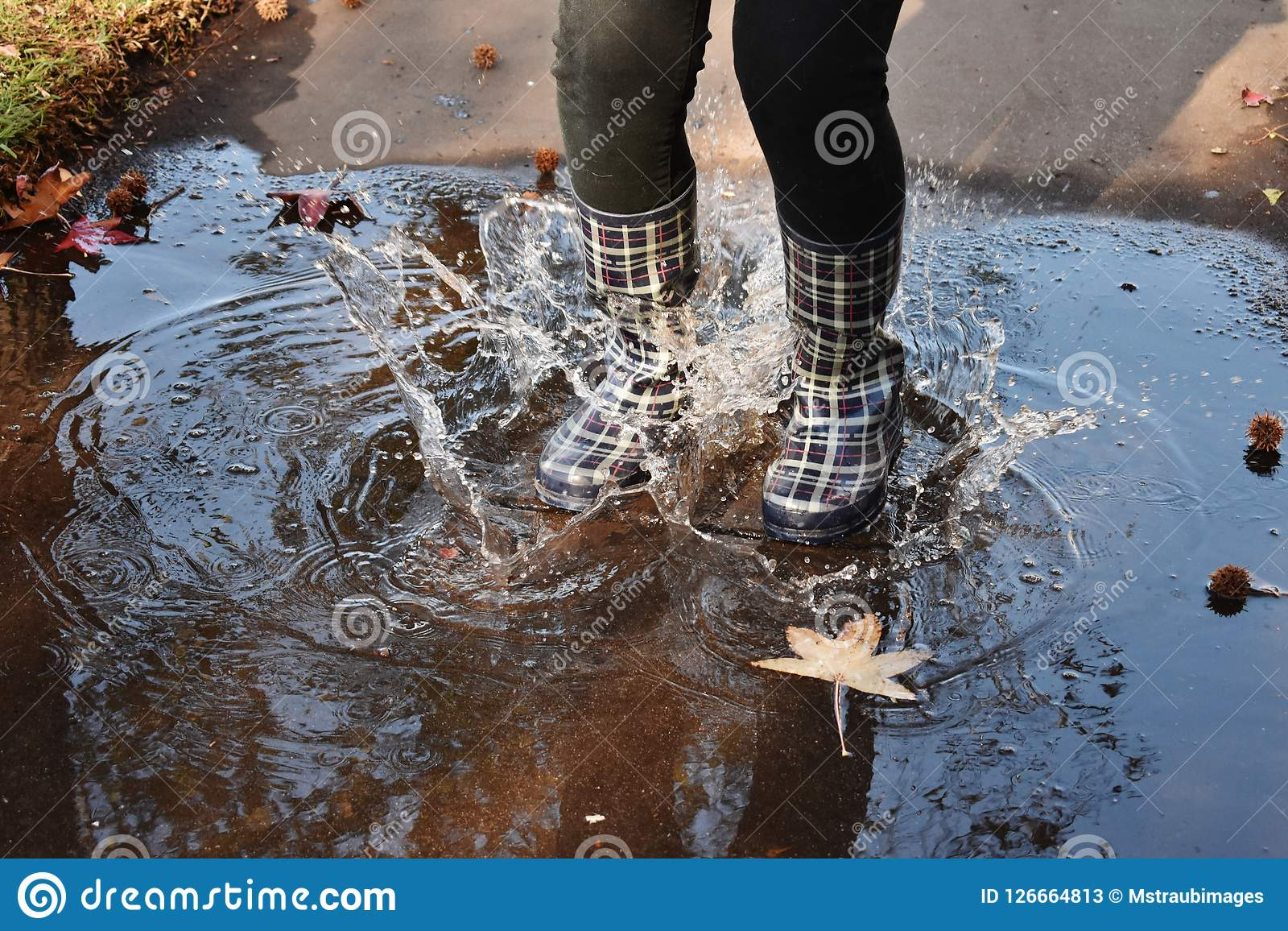 After the Rain. Plaid rain boots create swirls and splashes on the wet sidewalk Stock Photos