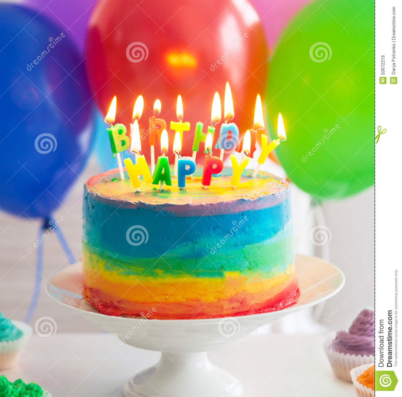 Rainbow Cake And Cupcakes Decorated With Birthday Candles Stock