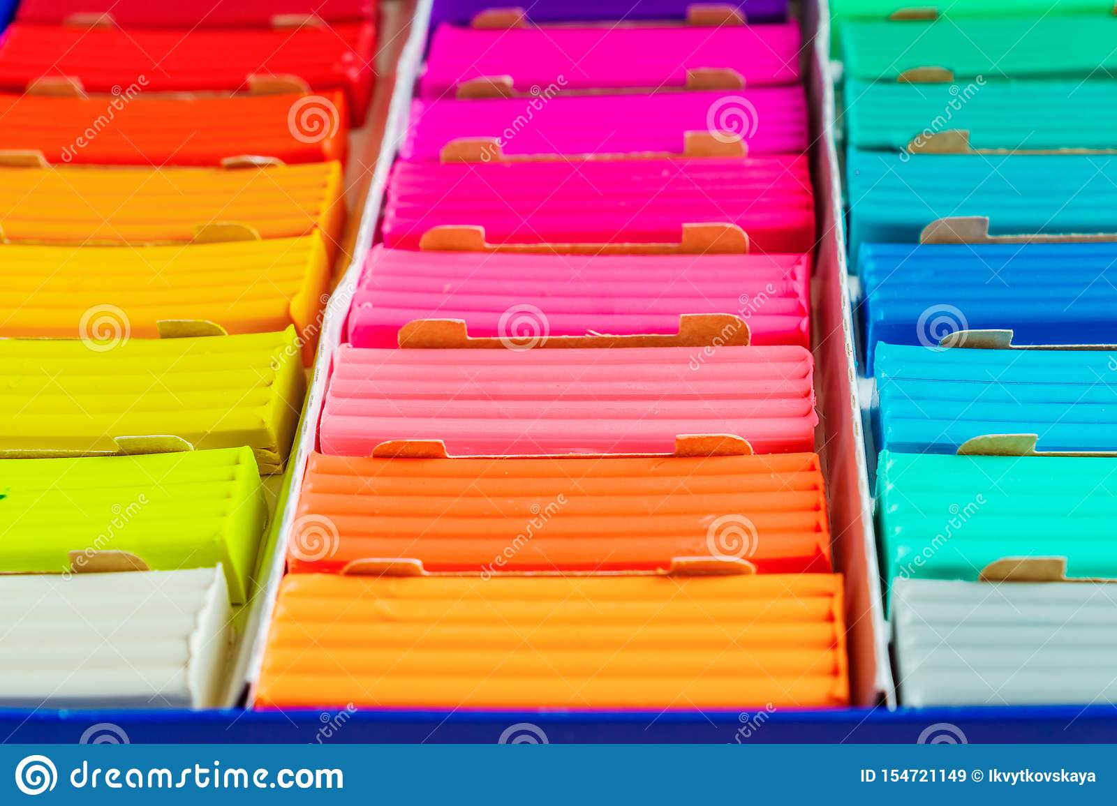 Rainbow colors of modeling clay. Multicolored plasticine bars ina box, background texture