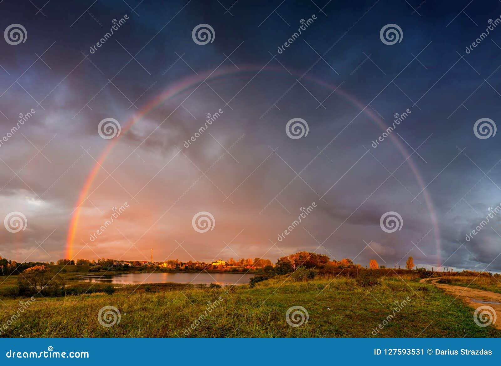 Rainbow landscape and dramatic rain sky