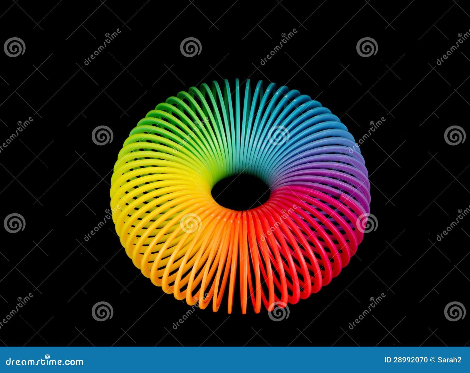 rainbow plastic spring on black background stock photo