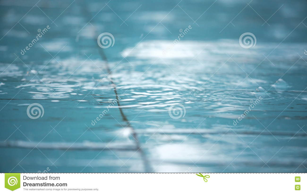 raindrops falling on white tile floor and forming bubbles stock