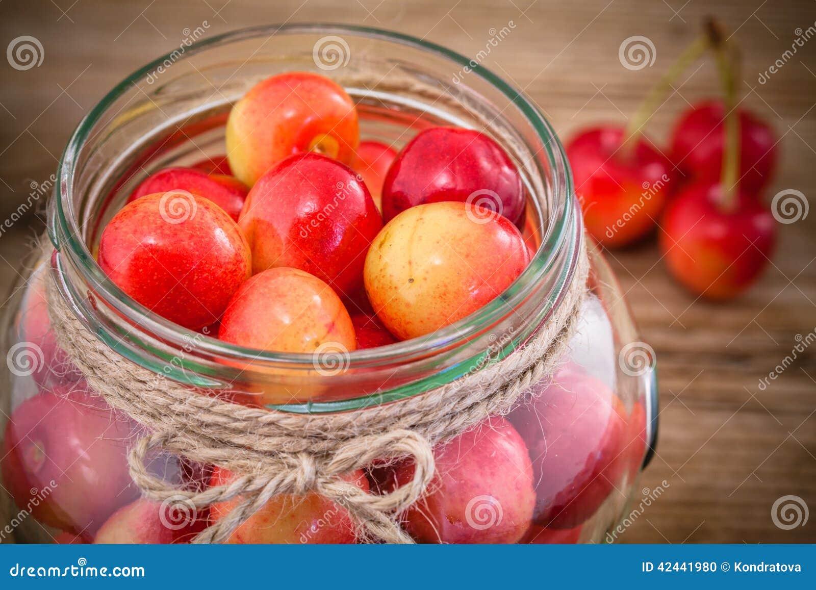 Rainier Cherries en vidrio en fondo de madera