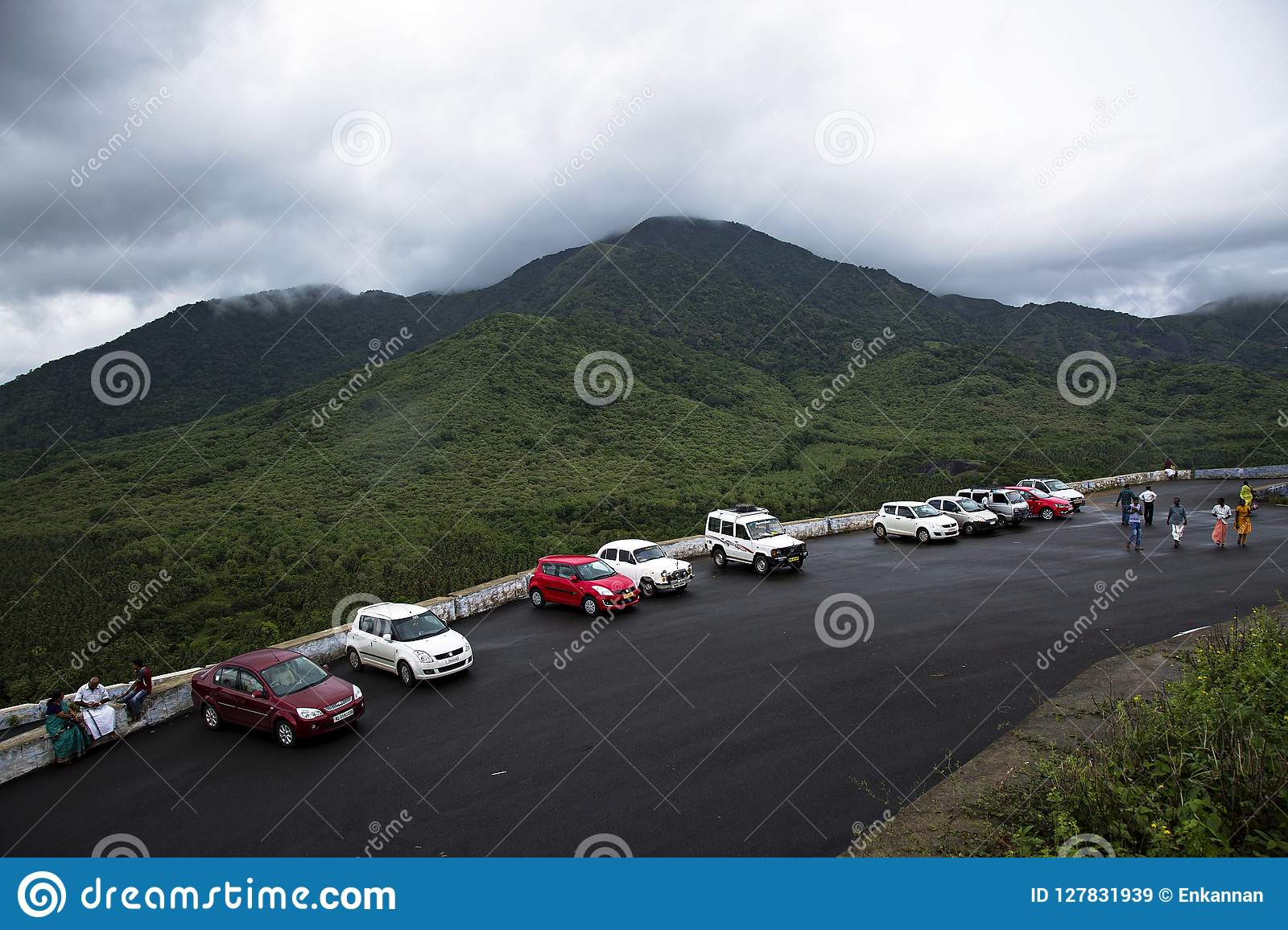 On a rainy day cars are parked at a hill stationin a row