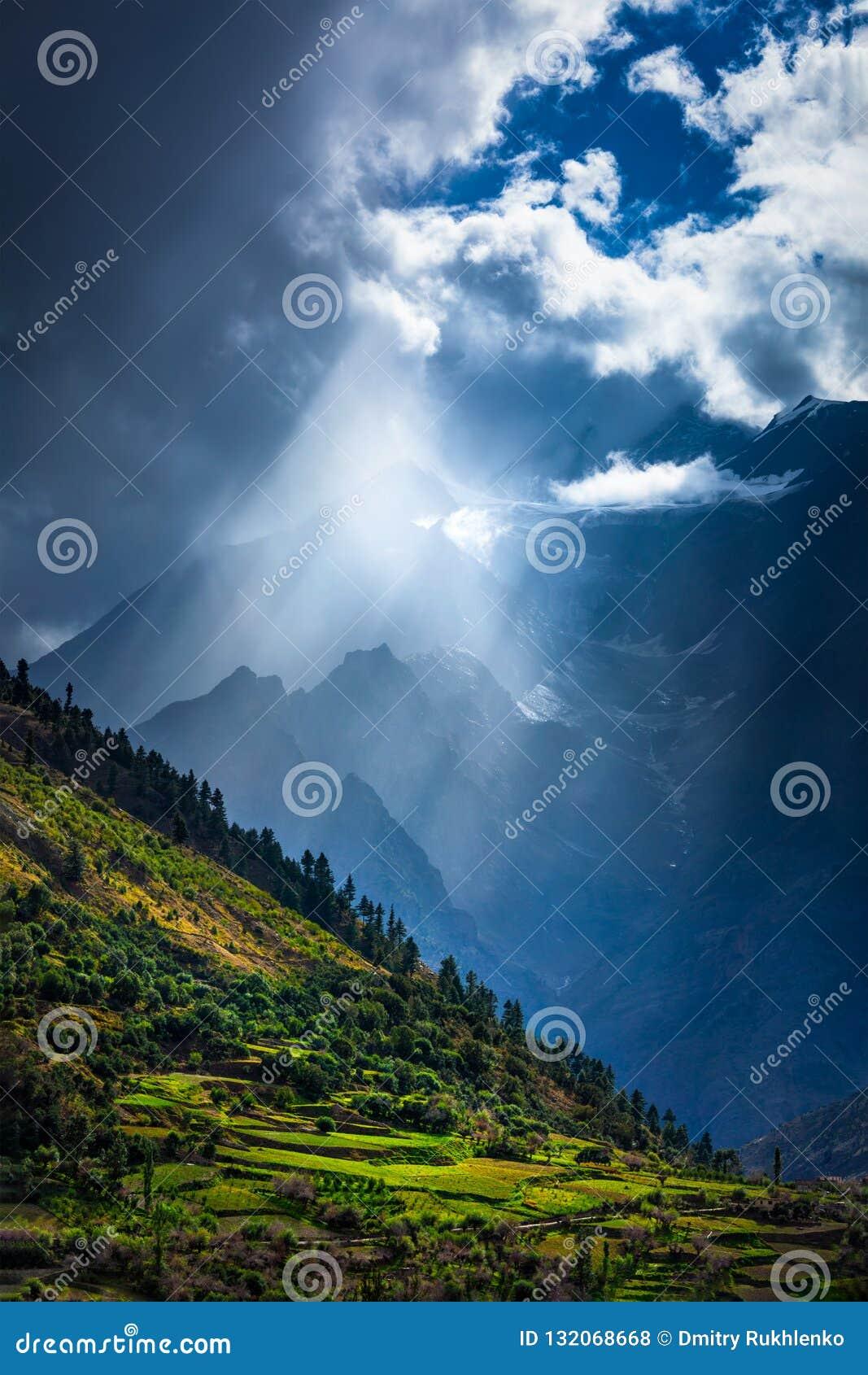 Raios de Sun através das nuvens no vale Himalaia nos Himalayas