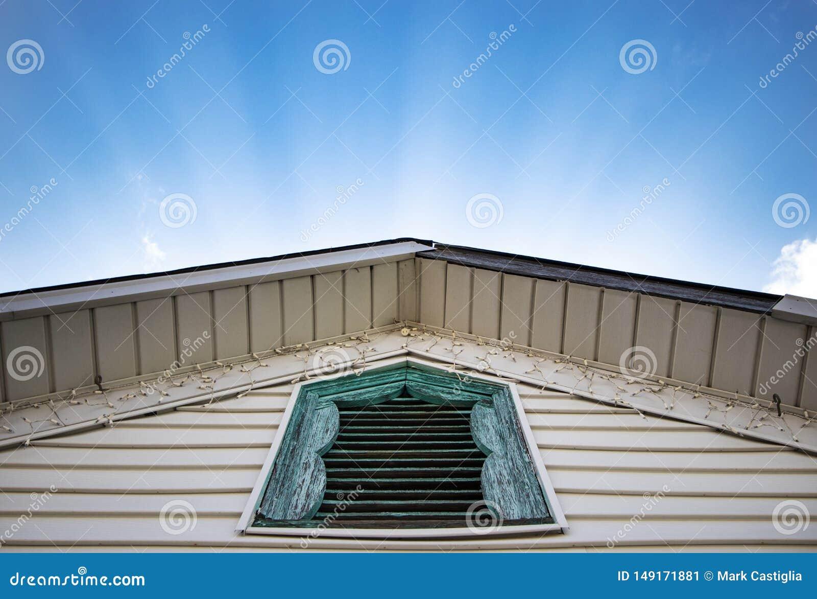 Raios ensolarados que brilham atr?s do telhado repicado com a janela azul r?stica