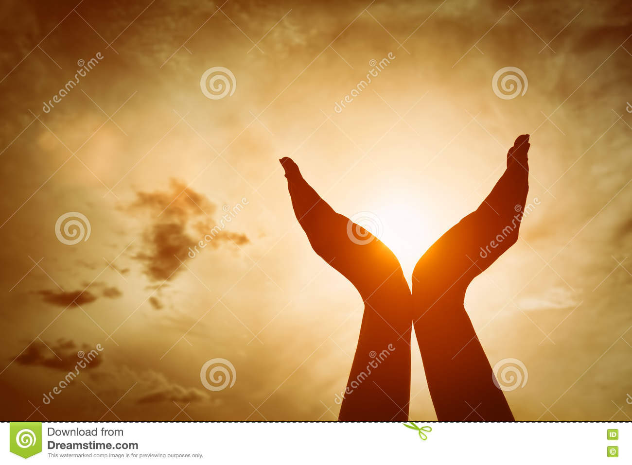 Raised hands catching sun on sunset sky. Concept of spirituality, wellbeing, positive energy