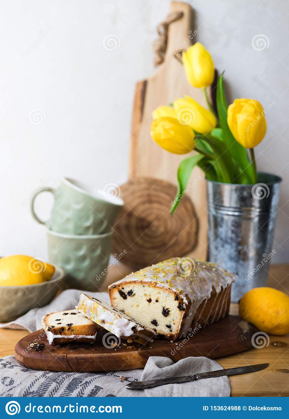 Raisin cake on a wooden board with lemon and yellow tulips